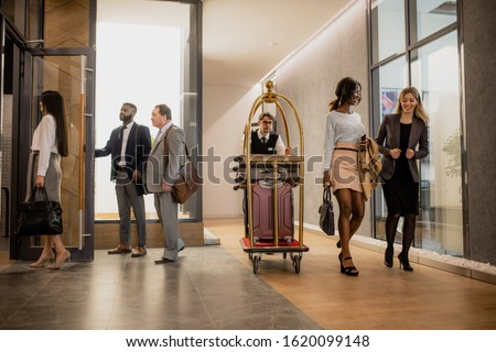 Busy porter pushing cart with baggage while moving among business people interacting on the move in hotel corridor Сток-фото ©