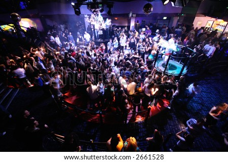 BUSY RAVE DANCEFLOOR FULL OF CLUBBERS AND RAVERS DANCING TO LOUD MUSIC