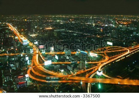 stock photo : Busy road intersection in the heart of downtown Bangkok, shot at night showing car headlight trails