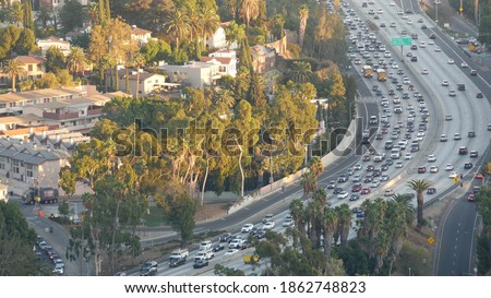 Busy rush hour intercity highway in metropolis, Los Angeles, California USA. Urban traffic jam on road in sunlight. Aerial view of cars on multiple lane driveway. Freeway with automobiles in LA city. Stock fotó ©
