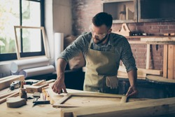 Busy skilled masterful experienced confident bearded dressed in checkered shirt and apron is taking wooden frame's measurements