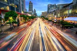 Busy street in the city at dusk, full of car light streaks; dynamic blue hour shot with long exposure motion blur effect