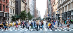 Busy street scene in New York City with groups of people walking across a crowded intersection on Fifth Avenue in Midtown Manhattan NYC