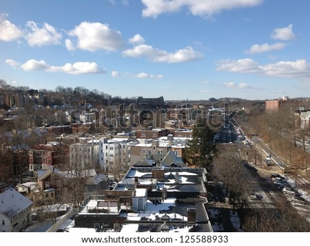 Busy street with houses and buildings under blue sky, suburban Boston