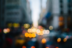 Busy street with varicolored lights of shop windows and cars in evening time against blurred background of New York city