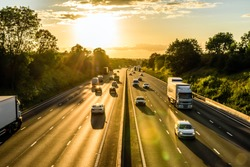 busy traffic on uk motorway road overhead view at sunset