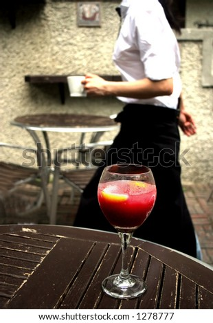 Busy waitress working in a city restaurant glides by a table with a glass of red wine - stock photo