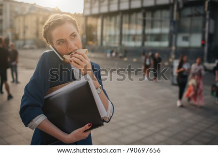Busy woman is in a hurry, she does not have time, she is going to eat snack on the go. Worker eating, drinking coffee, talking on the phone, at the same time. Businesswoman doing multiple tasks
