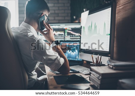 Busy working day at work. Rear view of young man in casual wear talking on the phone and working while sitting at the desk in creative office