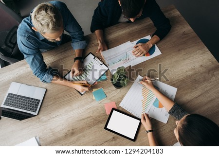 Busy working day. Top view of young modern people in stylish casual wear they talking about business while working in the creative office