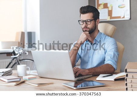 Busy working. Pensive young handsome man wearing glasses working on laptop and keeping hand on chin while sitting at his working place