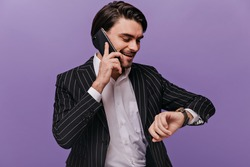Busy young gentleman with brunette hair, white shirt and black striped suit talking on phone, looking at watch and smiling against violet background. Business concept