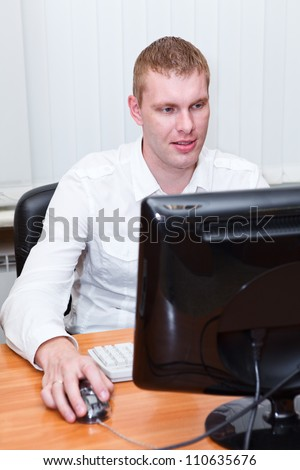 Busy young man in white shirt sitting at pc computer and working