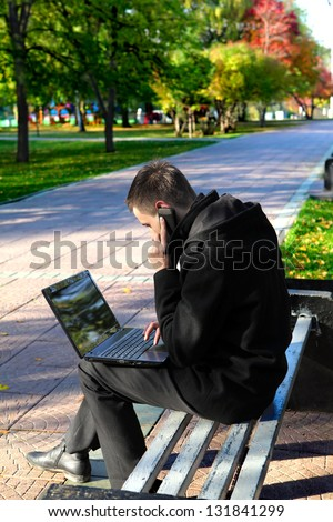 Busy Young man with Laptop sitting on the bench at the Autumn Park and Talking on Mobile Phone