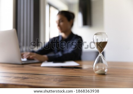 Busy young mixed race woman working studying by laptop on blurred background doing urgent job taking exam. Focus on close up sand glass posed on desk at home office. Measuring time. Deadline is coming Stock fotó ©