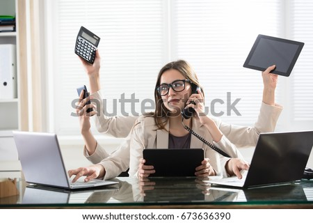Busy Young Smiling Businesswoman With Six Arms Doing Different Type Of Work In Office