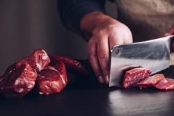 Butcher hands close up: cutting meet