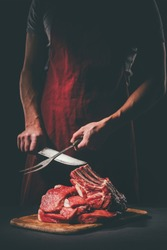 butcher sharpening knife to cut raw meat on wooden cutting board