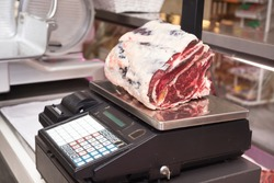 Butcher weighing meat at display cabinet in the butchery
