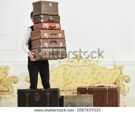 Butler and service concept. Macho, elegant porter carries heavy pile of vintage suitcases. Man with beard and mustache wearing classic suit delivers luggage, luxury white interior background #1087659335