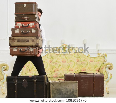 Butler and service concept. Man with beard and mustache wearing classic suit delivers luggage, luxury white interior background. Macho elegant on strict face carries pile of vintage suitcases.