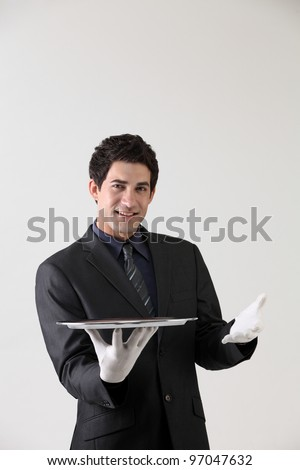 Butler holding an empty silver tray