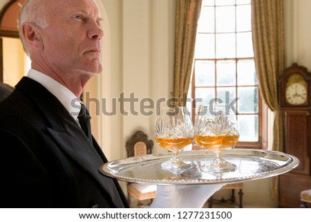 Butler in country house carrying tray of alcoholic drinks