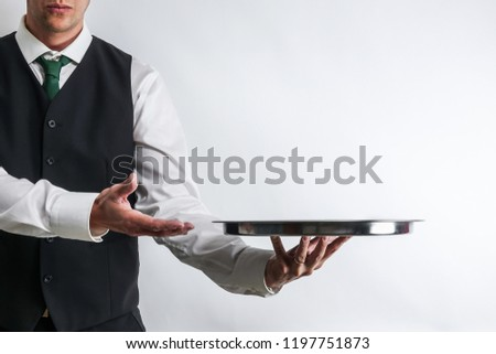Butler / waiter in white shirt and black suit vest carrying an empty silver tray. Copy space for text on white background. ストックフォト ©