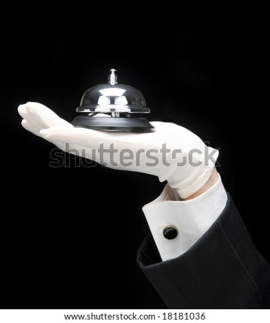 Butlers outstretched hand and arm with service bell.