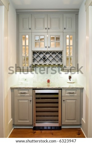 butlers pantry with wine rack, cabinets, and wine refrigerator