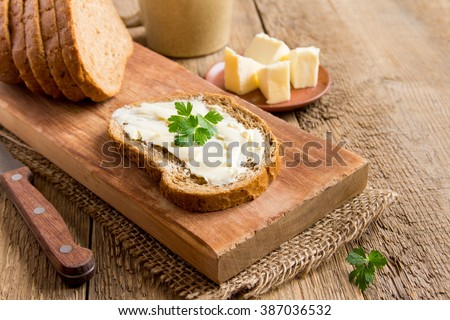Butter and bread for breakfast, with parsley over rustic wooden background with copy space
