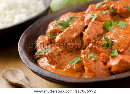 Butter chicken curry with basmati rice and limes.