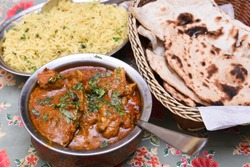 Butter chicken is a hot and spicy curry dish marinated in a savory mixture of Rajasthani spices,  garnished with fresh coriander leaves with pulao and roti Jaipur Rajasthan India. North Indian cusine