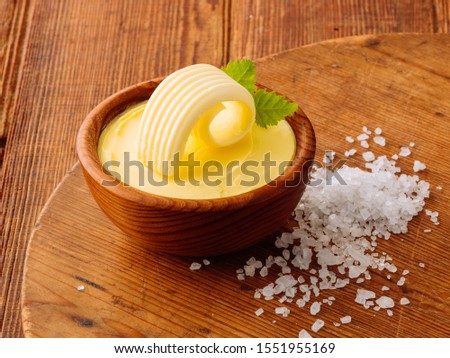 Butter curl with butter in a bowl and sea salt on wooden background