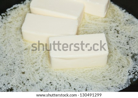 Butter melting on frying pan in preparation for cooking food.