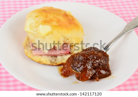 Butter melting on golden brown hot biscuit, fresh from oven, on white plate with spoon of fig preserves and slice of ham -- against pastel pink gingham country style background.