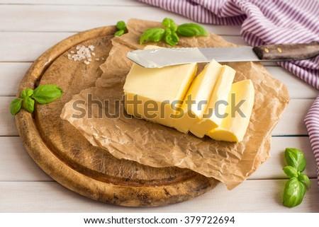 Butter. Slice of butter. Fresh sliced butter on the wooden plate.