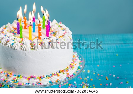 Buttercream birthday cake with colorful sprinkles and Candles over blue background