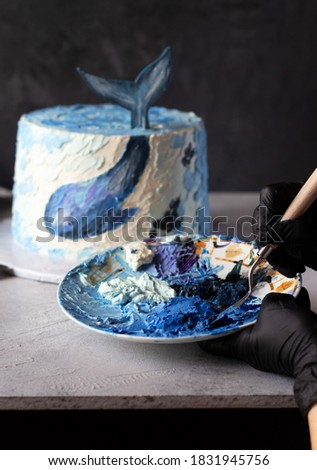 Buttercream palette with palette knife in chef's hand, cake painting process
