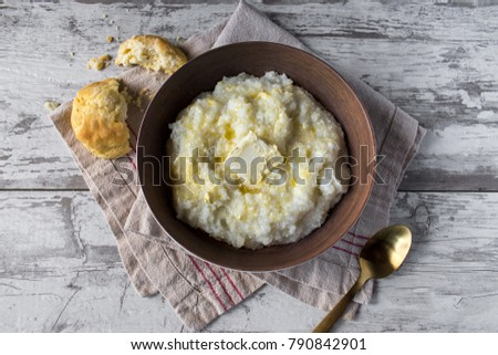 buttered grits with biscuits in rustic setting top view