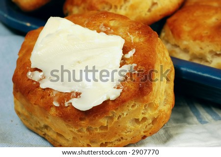 Buttered homemade buttermilk biscuit with a vintage blue dish filled with biscuits - stock photo