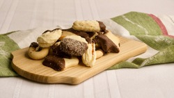 Buttered petit-fours with chocolate, placed on a wooden plate on a checkered napkin, on a table with white tablecloth.