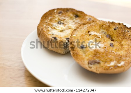 Buttered, toasted teacake on white plate