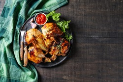 Butterflied grilled whole chicken on a black platter with ketchup, cutlery, parsley sprigs, garlic on a wooden table, view from above, copy space