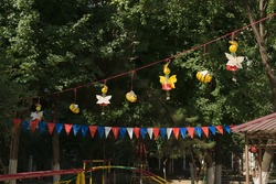 Butterflies and bees are made of plastic bottles and colorful flags hang on a rope against a tree background on a children's playground