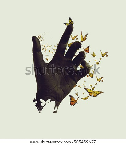 Butterflies flying out and around of black painted female hand on isolated background. Silhouette image, vintage sepia style. Conceptual, abstract. Freedom, dreaming, spiritual, reborn
