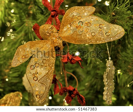Butterfly Christmas ornament hanging from a branch with red bows.