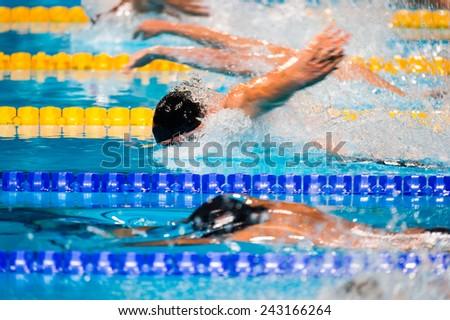 Butterfly men swimming race on swimming pool