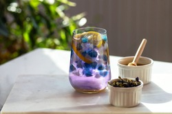 Butterfly-pea flower tea. Blue ice from anchan tea with lemon and honey. A drink to boost immunity. Adaptogen. Healthy lifestyle. Bright sunlight. Hard shadows. Blurred background. Close-up