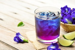Butterfly pea or blue pea juice ice cool drink with lime on wooden table.